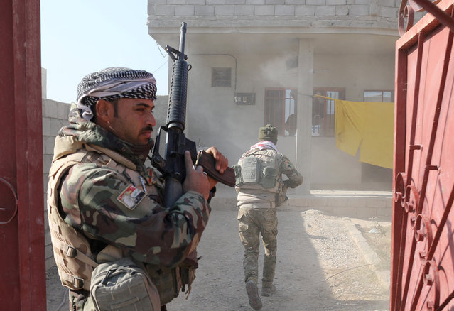 Iraqi soldiers prepare to search a house damaged during clashes with Islamic State fighters in Al-Qasar, South-East of Mosul, Iraq November 28, 2016. (Photo by Goran Tomasevic/Reuters)