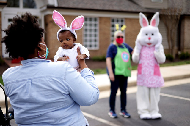 A woman holds her baby as they approach a person dressed as an Easter Bunny during a Bunny Drive-Thru event outside Kingstowne Snyder Fitness Center March 27, 2021 in Alexandria, Virginia. Kingstowne Residential Owners Corporation held the community event instead of the usual annual egg hunt for neighborhood children to celebrate Easter in a safer environment under the COVID-19 pandemic. (Photo by Alex Wong/Getty Images)