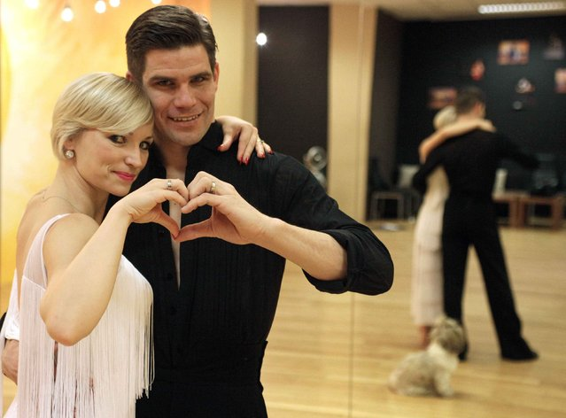 Professional dancers Jurij and Jagoda Batagelj make a heart-shaped gesture at a ballroom in Ljubljana February 11, 2015. (Photo by Srdjan Zivulovic/Reuters)