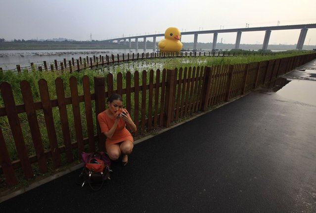 A television journalist does her make-up before reporting about an inflated Rubber Duck by Dutch conceptual artist Florentijn Hofman floating on a lake at the venue of the 9th China International Garden Expo in Beijing, September 6, 2013. The 18-metre-high inflatable sculpture, which made its first public appearance in the city on Friday, will be shown at the expo until September 23, after which it will be transported to the Summer Palace for display for another month, local media reported. (Photo by Petar Kujundzic/Reuters)