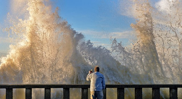A man watches as high surf crashes into the wall and spills onto Channel Drive in Montecito, Calif., January 7, 2016. Bacteria levels can increase significantly during and after rainstorms as contaminants in the runoff enter the ocean via storm drains, creeks and rivers. (Photo by Mike Eliason/AP Photo)