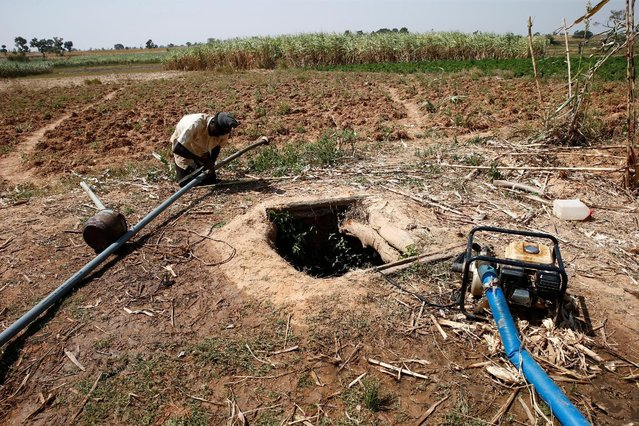 A man repairs a pipe used for irrigation near a well dug on a farm on the outskirts of Zaria in Nigeria's northern state of Kaduna November 15, 2016. (Photo by Akintunde Akinleye/Reuters)