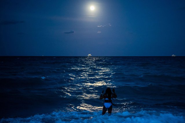 A woman stands in the water under the glow of the Super Pink Full Moon reflected in the ocean in Miami Beach, on April 26, 2021. (Photo by Chandan Khanna/AFP Photo)