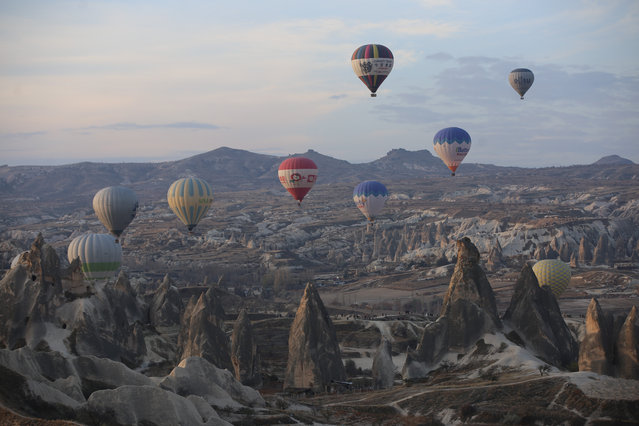 A drone photo shows a view of hot air balloons gliding over Goreme district during early morning at the historical Cappadocia region, located in Central Anatolia's Nevsehir province, Turkey on November 24, 2019. Cappadocia is preserved as a UNESCO World Heritage site and is famous for its chimney rocks, hot air balloon trips, underground cities and boutique hotels carved into rocks. In Turkey's one of the most important tourism regions Cappadocia, local and foreign tourists get the chance of enjoying the scenery participating air balloon tours in the early hours of the morning. (Photo by Behcet Alkan/Anadolu Agency via Getty Images)