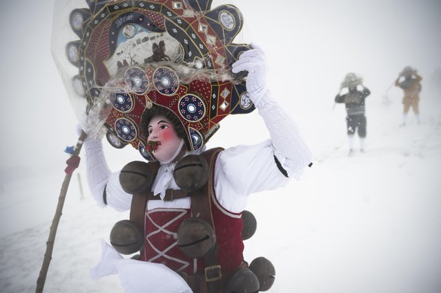 A  traditional masked  so-called Silvesterchlaus is on his way in Waldstatt, Switzerland, Wednesday, January13, 2016, to offer the best wishes for the New Year (following the Julian calendar) to the farmers in this region. After their performance of singing and dancing the Silvesterchlaeuse receive hot drinks. (Photo by Gian Ehrenzeller/Keystone via AP Photo)