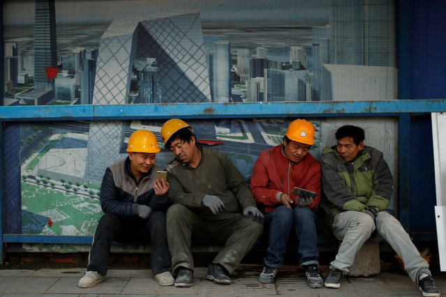 Workers look at mobile phones as they sit outside a construction site in Beijing, China December 6, 2016. (Photo by Thomas Peter/Reuters)