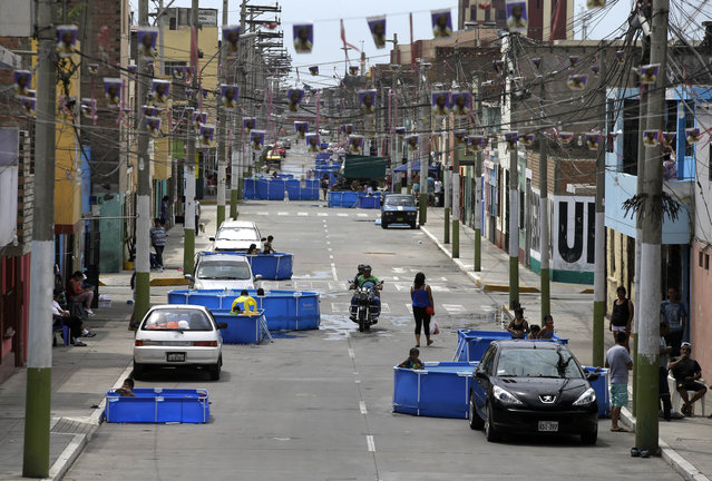 In this Sunday, February 15, 2015 photo, plastic pools dot a city block street in Callao, Peru. (Photo by Martin Mejia/AP Photo)