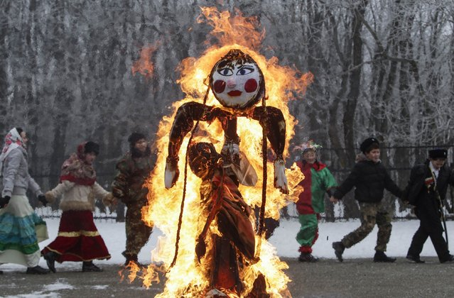 Children walk around a burning effigy of Lady Maslenitsa, as they celebrate Maslenitsa, or Pancake Week, in Stavropol, Russia February 21, 2015. Maslenitsa is widely viewed as a pagan holiday marking the end of winter and is celebrated with pancake eating, while the Orthodox Church considers it as the week of feasting before Lent. (Photo by Eduard Korniyenko/Reuters)