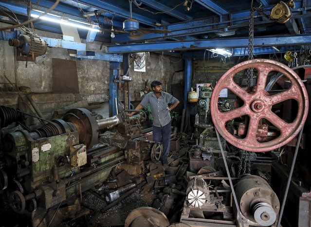 A worker looks on as he operates a machine making gear parts for cranes, inside a workshop in an industrial area in Mumbai, India, January 12, 2016.  India's annual industrial output contracted 3.2 percent in November, government data showed on Tuesday. (Photo by Danish Siddiqui/Reuters)