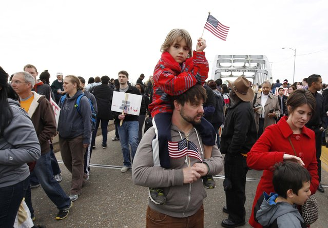 Moises Mason sits on his father Jeff's shoulders as their family walk along the Edmund Pettus Bridge before the beginning of the 50th anniversary of the Selma to Montgomery civil rights march in Selma, Alabama March 8, 2015. REUTERS/Tami Chappell  (UNITED STATES - Tags: POLITICS ANNIVERSARY SOCIETY)