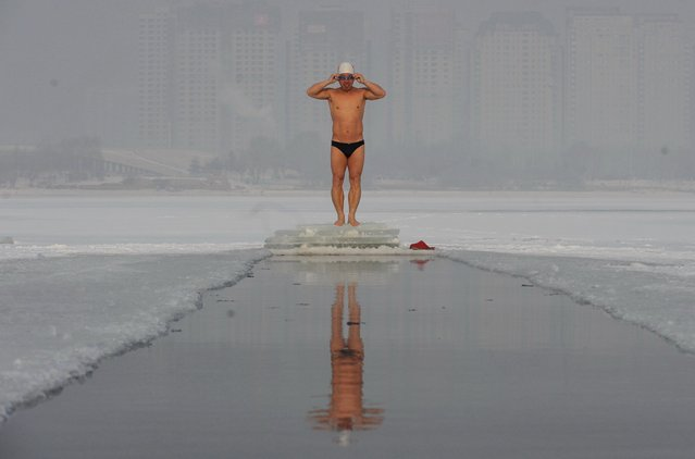 A winter swimmer prepares for a swim in a pool dug out on the ice-covered river in Shenyang in northeast China's Liaoning province, December 15, 2016. (Photo by FeatureChina/Newscom)