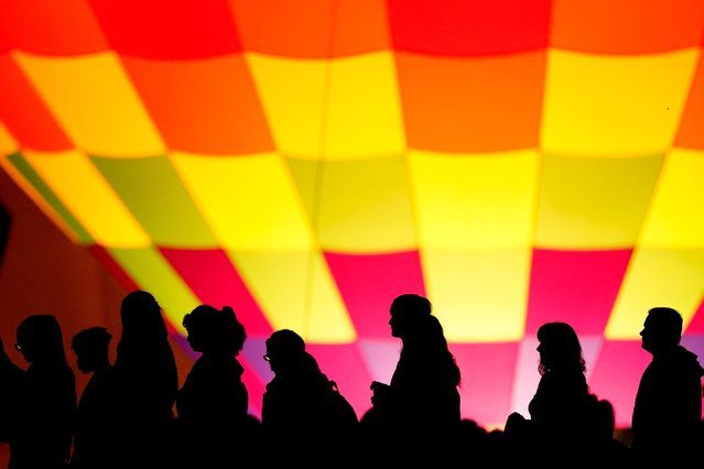 People are silhouetted against a hot air balloon during a balloon glow as part of Memorial Day weekend activities on the grounds of the National World War I Museum and Memorial, Sunday, May 30, 2021, in Kansas City, Mo. (Photo by Charlie Riedel/AP Photo)