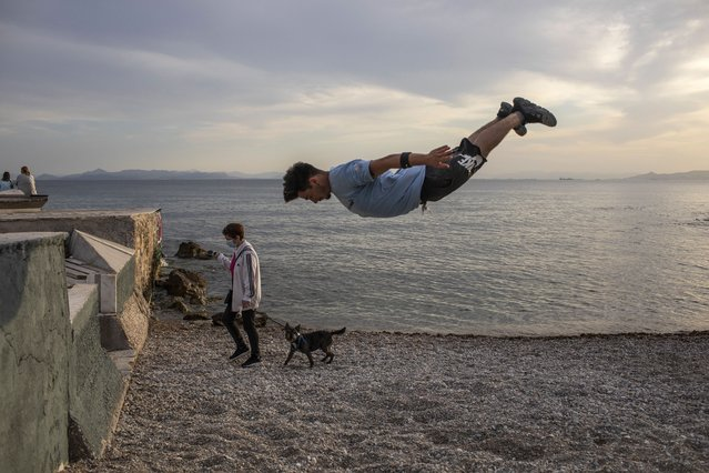 25 year-old Jimmakos Scotis makes a backflip as a woman wearing a protective face mask walks with her dog at the seaside of Alimos, suburb of Athens, on Tuesday, May 4, 2021. Greece began easing coronavirus-related restrictions with a view to opening to the vital tourism industry in the summer. (Photo by Petros Giannakouris/AP Photo)