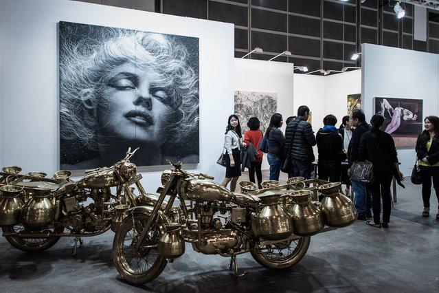 Visitors are seen next to an artwork by Korean artist Hyung Koo Kang (L) during the opening of the Art Basel art fair for a VIP preview in Hong Kong on March 13, 2015. Hong Kong's biggest art fair, Art Basel, opened its doors with thousands of visitors expected over the next five days. (Photo by Philippe Lopez/AFP Photo)