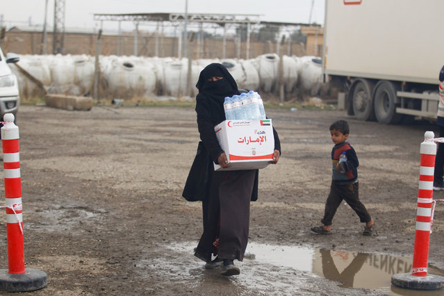 A displaced Iraqi woman, who fled the Islamic State stronghold of Mosul, receives aid in the east of Mosul, Iraq, December 21, 2016. (Photo by Khalid al Mousily/Reuters)