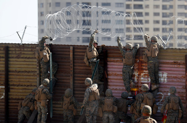 U.S. Marines instal concertina wire along the top of the primary border wall at the port of entry next to Tijuana in San Ysidro, San Diego, U.S., November 9, 2018. (Photo by Mike Blake/Reuters)