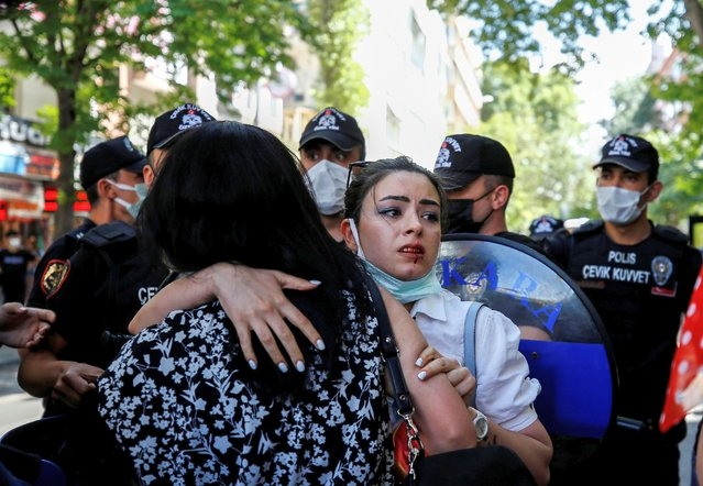 An injured demonstrator hugs another as riot police officers prevent them from attending a Pride parade, which was banned by local authorities, in central in Ankara, Turkey on June 29, 2021. (Photo by Cagla Gurdogan/Reuters)