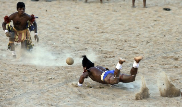 A member of indigenous group Pares dives to head the ball during an exhibition game of soccer where only heads are used to play the game, during the XII Games of the Indigenous People in Cuiaba November 10, 2013. 48 Brazilian Indigenous tribes will present their cultural rituals and compete in traditional sports such as archery, running with logs and canoeing during the XII Games of Indigenous People which will run until November 16. (Photo by Paulo Whitaker/Reuters)