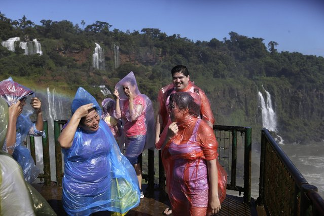 In this March 15, 2015 photo, people wear plastic to try to keep dry in the spray of Iguazu Falls in Brazil. Spray from the falls douses the nearby viewing areas where some tourists don rain ponchos while others take off their shirts and dance and hug in the drenching mist. (Photo by Jorge Saenz/AP Photo)