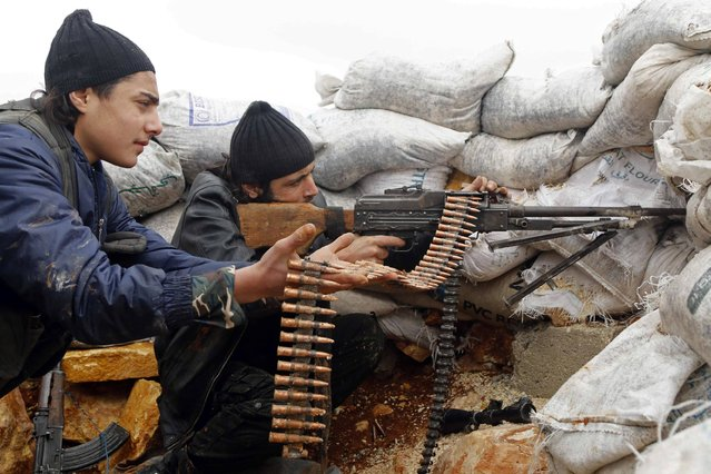Rebel fighters fire a weapon on the al-Breij frontline, after what they said was an advance by them in the Manasher al-Hajr area where the forces of Syria's President Bashar al-Assad were stationed, in Aleppo January 7, 2015. (Photo by Hosam Katan/Reuters)