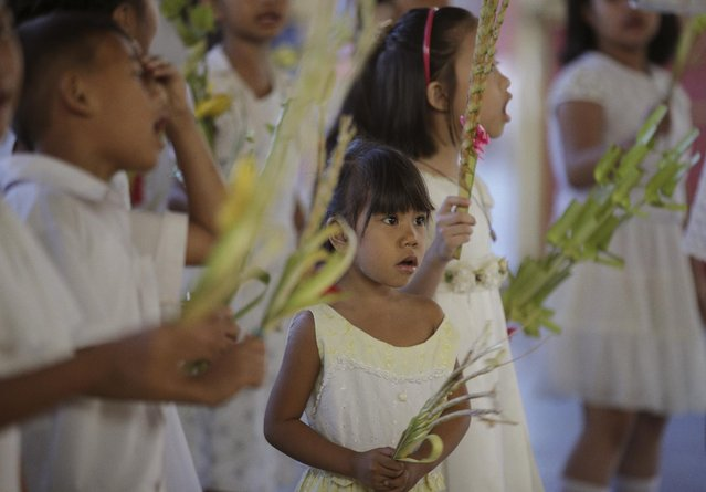Filipino children sing during Palm Sunday rites outside the Holy Family Parish church in suburban Quezon city, north of Manila, Philippines on Sunday, March 29, 2015. Palm Sunday marks the triumphant entry of Jesus Christ into Jerusalem and ushers in the Holy Week observance among Catholics worldwide. (Photo by Aaron Favila/AP Photo)