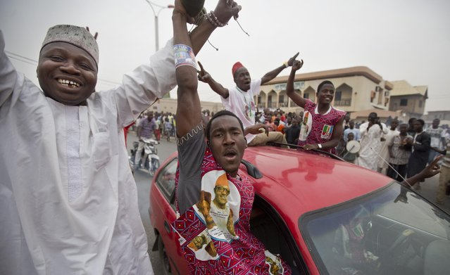 Supporters of opposition candidate Muhammadu Buhari celebrate an anticipated win for their candidate, in Kano, Nigeria Tuesday, March 31, 2015. Nigeria's aviation minister says President Goodluck Jonathan has called challenger Muhammadu Buhari to concede and congratulate him on his electoral victory, paving the way for a peaceful transfer of power in Africa's richest and most populous nation. (Photo by Ben Curtis/AP Photo)
