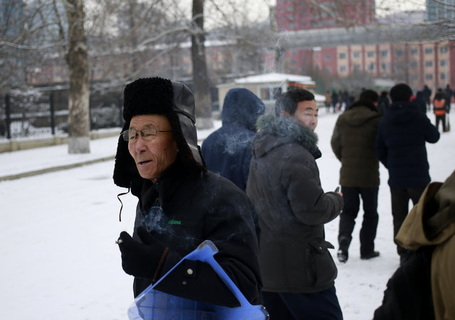 A North Korean man smokes a cigarette as he walks on a snow-covered street in Pyongyang, North Korea, where the winter season has started, on Sunday, December 16, 2018. (Photo by Dita Alangkara/AP Photo)