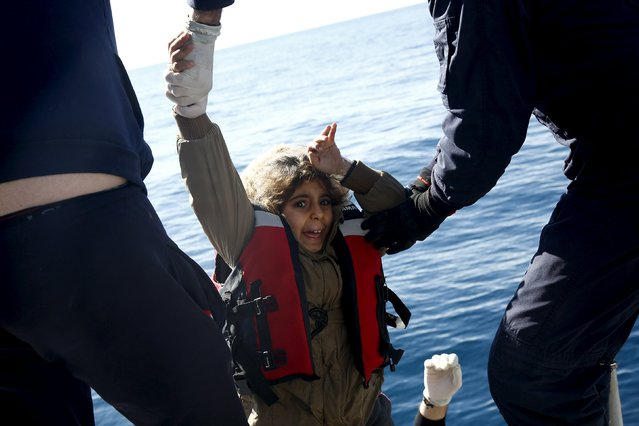 Greek Coast Guard officers move a girl from a dinghy carrying refugees and migrants aboard the Ayios Efstratios Coast Guard vessel, during a rescue operation in the open sea between the Turkish coast and the Greek island of Lesbos, February 8, 2016. (Photo by Giorgos Moutafis/Reuters)