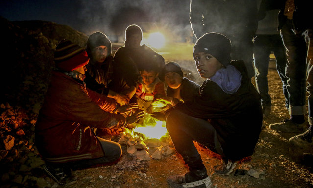 Syrians who flee the attacks of Syrian and Russian air forces, warm around the fire as they shelter at tents and try to hold on to life, at a refugee camp at the Bab al-Salameh border crossing on Turkish-Syrian border near Azaz town of Aleppo, Syria on February 08, 2016. (Photo by Fatih Aktas/Anadolu Agency/Getty Images)