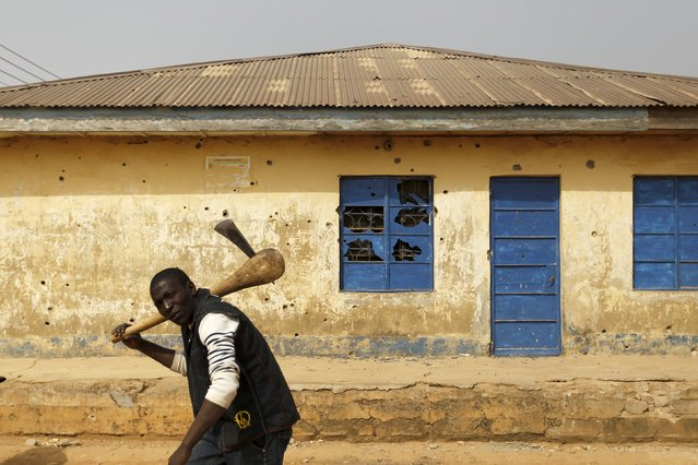 A man carrying an axe walks past a house marked with bullet holes in Gyallesu district after recent clashes between Shi'ites and the army in Zaria, Kaduna state, Nigeria, February 3, 2016. (Photo by Afolabi Sotunde/Reuters)