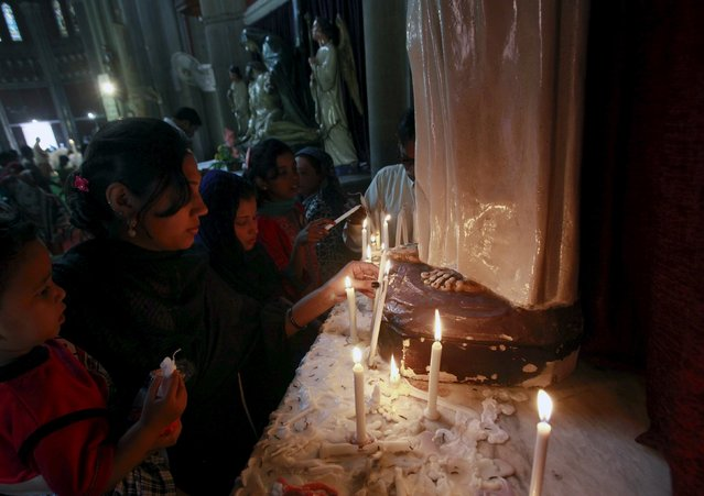 Pakistani Christians light candles in front of a religious statue during Easter celebrations at the Sacred Heart of Jesus Church in Lahore April 5, 2015. (Photo by Mohsin Raza/Reuters)