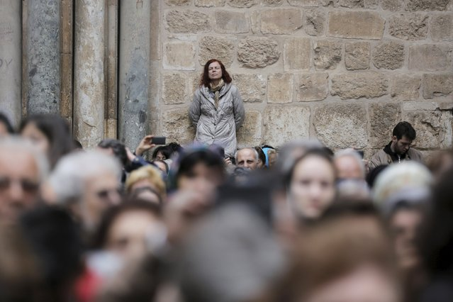 A woman leans against a wall as she participates in the washing of the feet ceremony outside the Church of the Holy Sepulchre in Jerusalem's Old City, April 9, 2015, ahead of Orthodox Easter. (Photo by Ammar Awad/Reuters)
