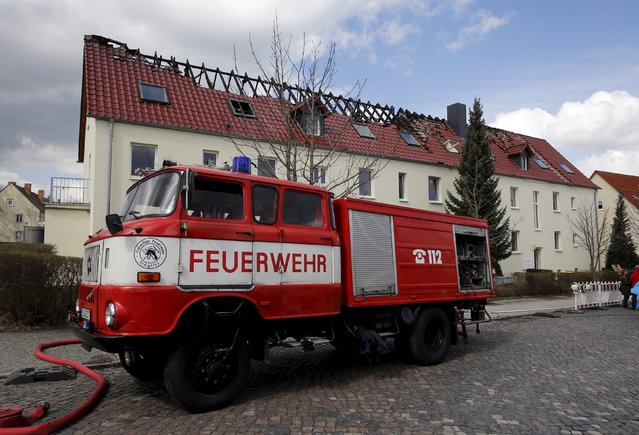A fire truck is seen in front of a building damaged by a fire, which will be used as an asylum seekers home, in Troeglitz, Germany April 4, 2015. Authorities are investigating the reason of the fire which destroyed the roof, police said. (Photo by Fabrizio Bensch/Reuters)