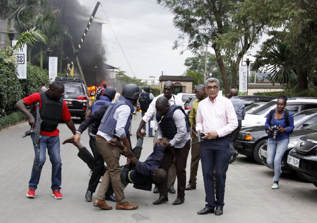 Security forces help a man at the scene of a blast in Nairobi, Kenya Tuesday, January 15, 2019. Terrorists attacked an upscale hotel complex in Kenya's capital Tuesday, sending people fleeing in panic as explosions and heavy gunfire reverberated through the neighborhood. (Photo by Khalil Senosi/AP Photo)
