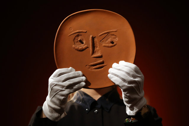 """A member of staff poses with an unglazed terracotta plate entitled """"Visage aux grands yeux"""" by Pablo Picasso at Christie's auction house on February 17, 2016 in London, England. Forming part of the """"Queen Anne's Gate: Works from the Art Collection of Sting and Trudie Styler"""" auction on February 24, it is expected to fetch between 1,200-1,800 GBP. (Photo by Carl Court/Getty Images)"""