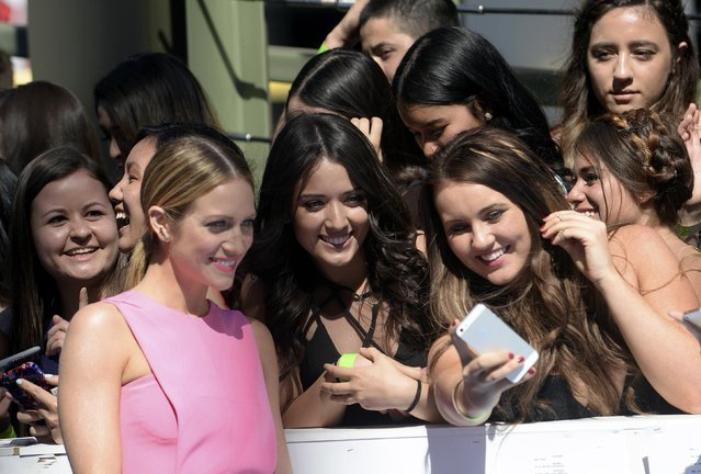 Actress Brittany Snow poses with fans as she arrives at the 2015 MTV Movie Awards in Los Angeles, California April 12, 2015. (Photo by Phil McCarten/Reuters)