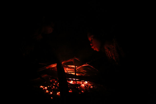 A child tries to re-light a fire at Kagorwa Pygmy camp on Idjwi island in the Democratic Republic of Congo, November 23, 2016. (Photo by Therese Di Campo/Reuters)