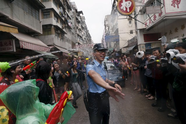 A police officer gets sprayed by water guns during Songkran Festival celebrations at Kowloon City district, known as Little Thailand as there is large number of restaurants and shops run by Thais, in Hong Kong April 12, 2015. (Photo by Tyrone Siu/Reuters)