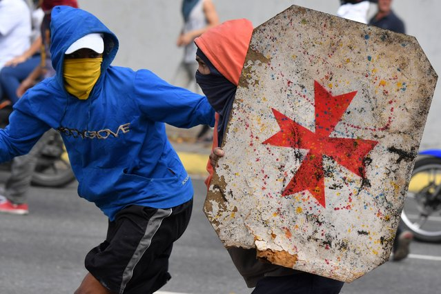Opposition demonstrators use a makeshift shield as they clash with security forces during a protest against the government of President Nicolas Maduro on the anniversary of the 1958 uprising that overthrew the military dictatorship, in Caracas on January 23, 2019. (Photo by Yuri Cortez/AFP Photo)