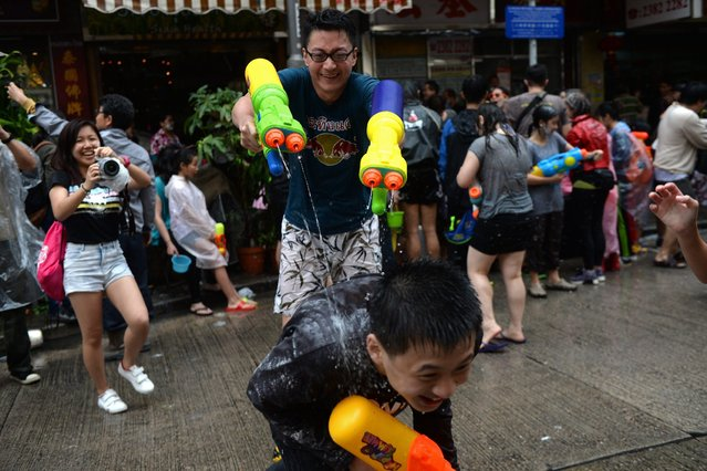 Revellers take part in a water fight to celebrate the Songkran festival in Hong Kong on April 12, 2015. The Songkran festival marks the start of the traditional new year in Thailand which begins on April 13. (Photo by Dale de la Rey/AFP Photo)