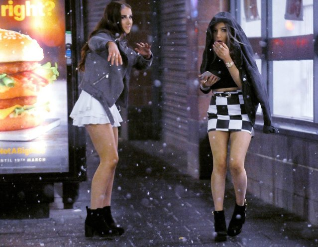 Two young women huddle up in their coats as they brave the cold in Newcastle, England on February 1, 2019. Women in skimpy dresses and men in t-shirts enjoyed a drink and a dance as they celebrated January finally being over. (Photo by Will Walker/North News and Pictures)