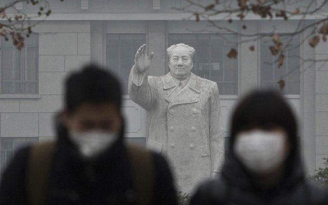 People wearing masks walk in front of the statue of late Chinese leader Mao Zedong in a university, during a hazy day in downtown Shanghai December 26, 2013. (Photo by Aly Song/Reuters)