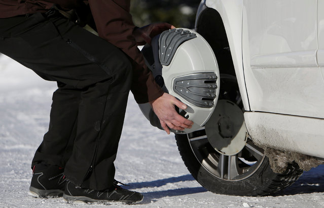 A man puts automatic snow chains on a car tire at the ski resort Ovcarna near the village of Karlova Studanka, Czech Republic, January 19, 2017. (Photo by David W. Cerny/Reuters)