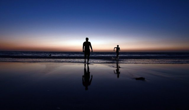 Indian youngsters enjoy the final moments of sunset on the beach along the Arabian Sea coast in Mumbai, India, 31 March 2015. (Photo by Divyakant Solanki/EPA)