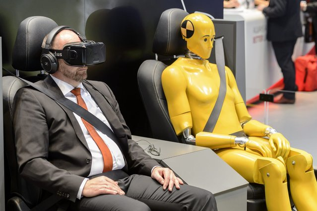 A journalist sits next to a dummy during a virtual Toyota test drive, during the press day at the 86th Geneva International Motor Show in Geneva, Switzerland, 01 March 2016. The Motor Show will open its gates to the public from 3th to 13th March presenting more than 200 exhibitors and more than 120 world and European premieres. (Photo by Martial Trezzini/EPA)