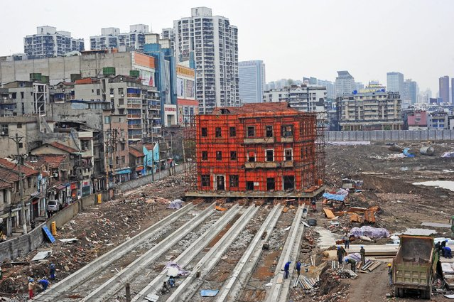 A historical building is seen being moved to make way for new constructions in Wuhan, Hubei Province, China, in this picture taken March 9, 2016. (Photo by Reuters/Stringer)
