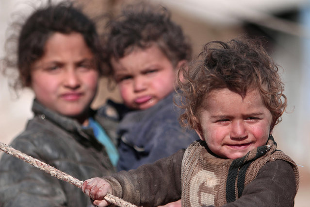 Internally displaced Syrian children who fled Raqqa city stand near their tent in Ras al-Ain province, Syria January 22, 2017. (Photo by Rodi Said/Reuters)