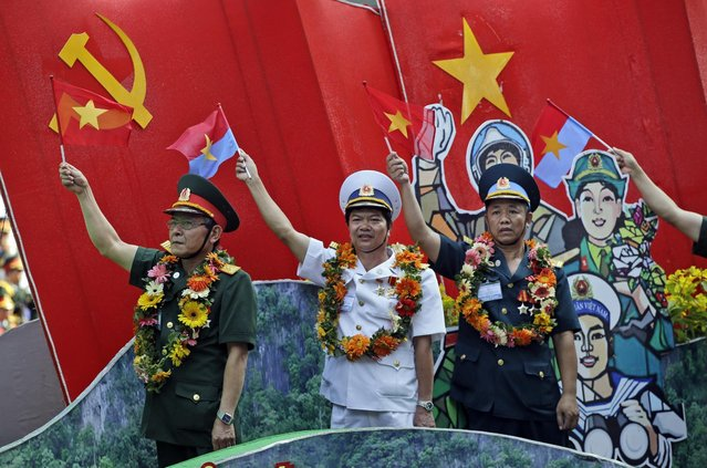 """Vietnamese military personnel wave flags during a parade celebrating the 40th anniversary of the end of the Vietnam War which is also remembered as the """"Fall of Saigon"""", in Ho Chi Minh City, Vietnam, Thursday, April 30, 2015. (Photo by Dita Alangkara/AP Photo)"""