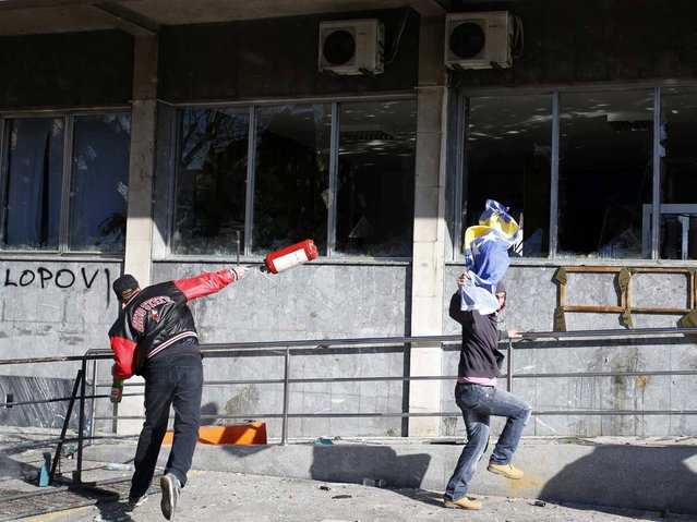 Protesters hurl items at a government building in Tuzla, February 7, 2014. (Photo by Dado Ruvic/Reuters)