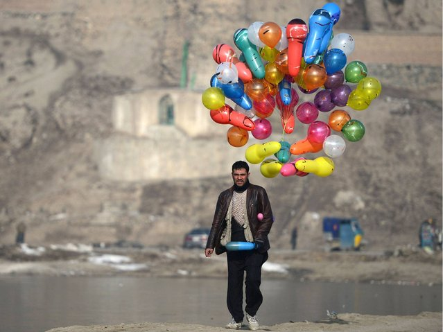 An Afghan man carries balloons as he walks at Shuhada Lake in Kabul on February 10, 2014. Afghanistan's economy is recovering from decades of conflict but despite the significant improvement in the last decade it is extremely poor, landlocked, and highly dependent on foreign aid. (Photo by Wakil Kohsar/AFP Photo)